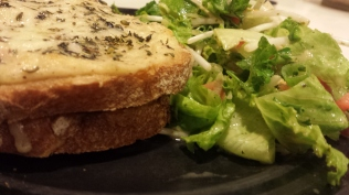 Croque-Monsieur with gruyere and herbs de provence accompanied by a lettuce, parsley, cucumber, tomato, and bean sprout salad in Goddess dressing.